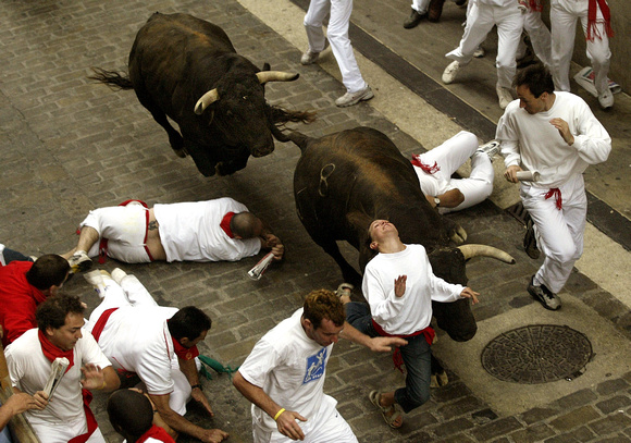 A runner is knocked down by a bull