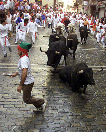 A runner avoids a falling fighting bull